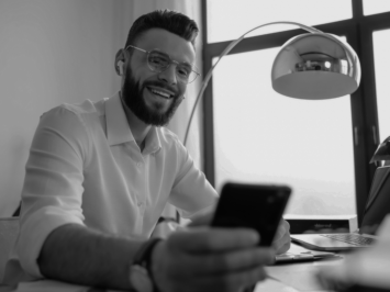 This image shows a young man smiling while looking at his phone.