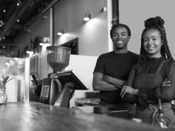 This image shows two owners of a small coffee shop smiling at their counter.